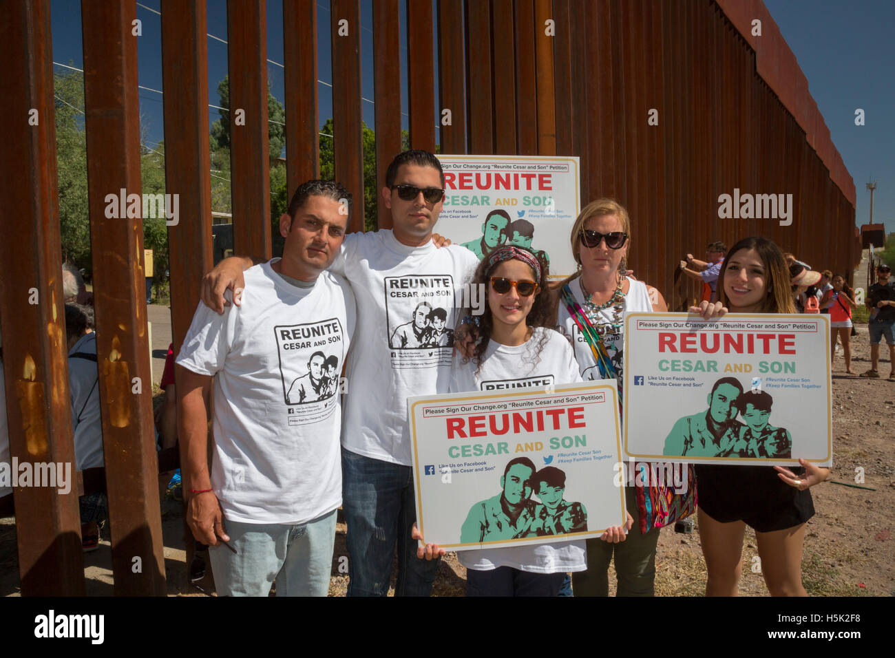 Nogales Mexico-Cesar Leyva (left) with family at the U.S.-Mexico border fence. Leyva was deported and separated - Stock Image