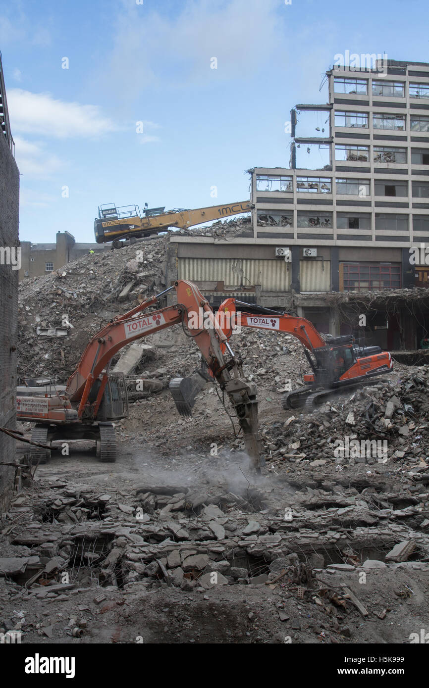 Heavy plant machinery wrecking and breaking up buildings on an inner city demolition site that looks like a war - Stock Image