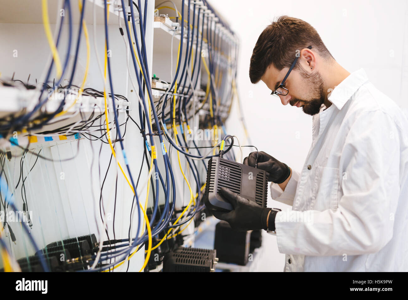 Network technician testing modems in factory - Stock Image