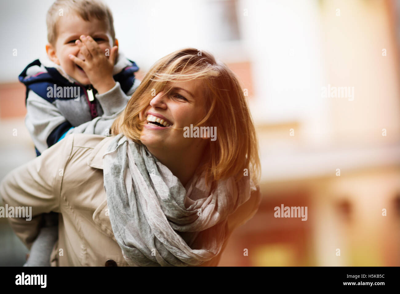 Happy mother and child smiling outdoors - Stock Image