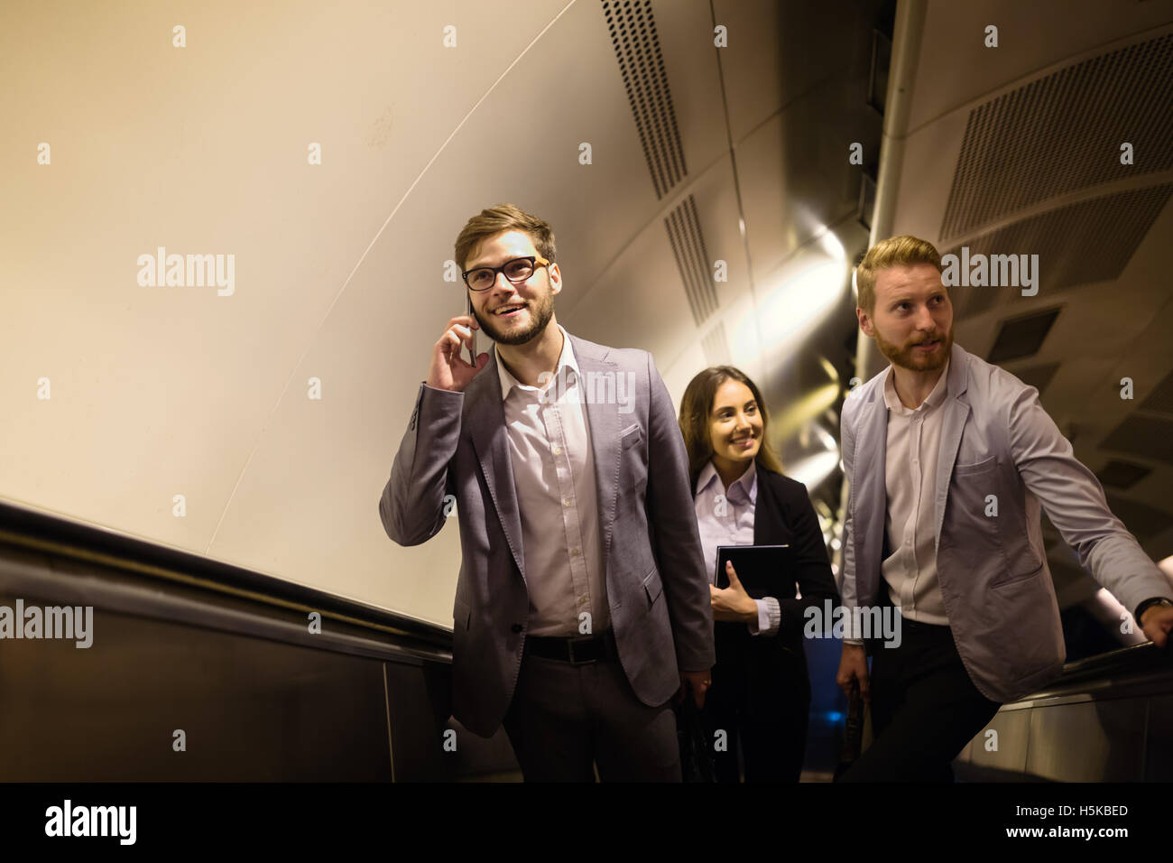 Businesspeople using subway as means of transport - Stock Image
