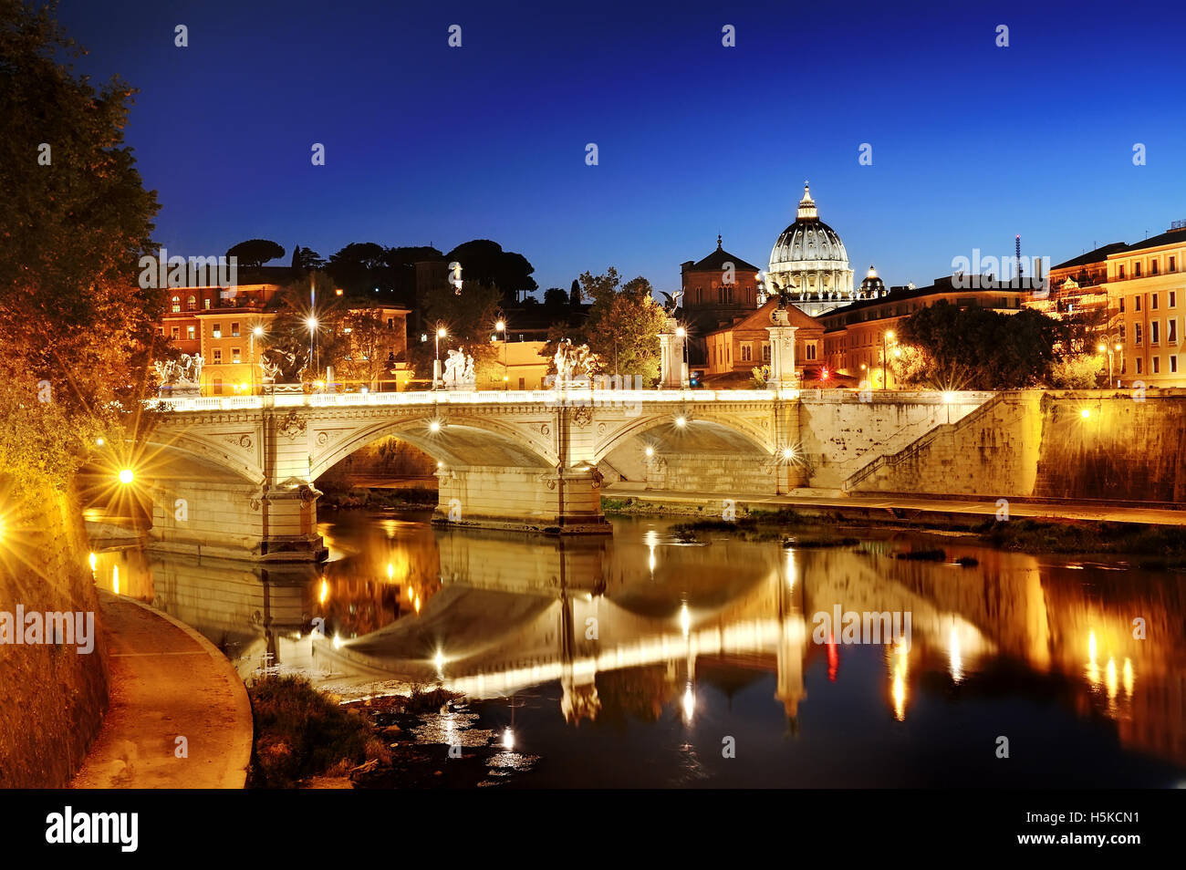 Rome, Italy - scenic view of a bridge over Tiber river and St. Peter's Basilica dome in Vatican at night - Stock Image