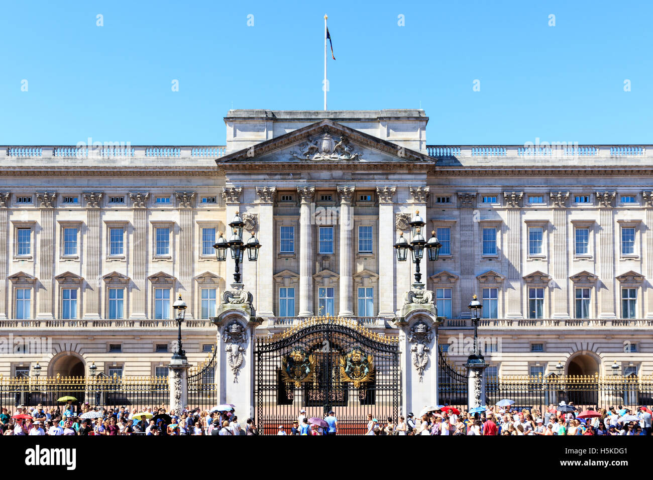 London, UK - July 19, 2016 - Buckingham Palace in London with a crowd of tourists outside on a cloudless day - Stock Image
