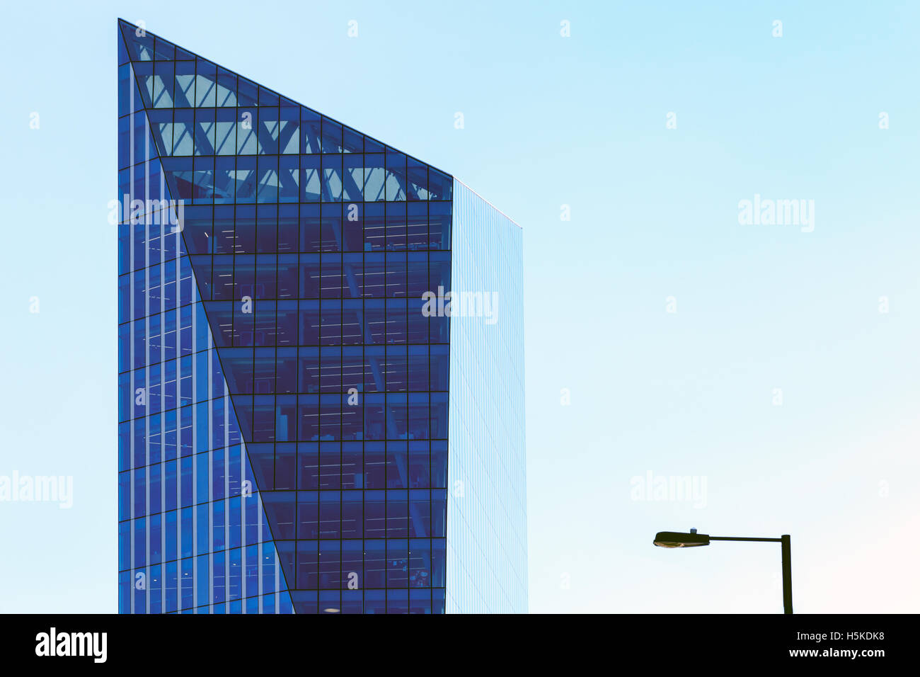 Modern office building (UBM headquarter) and a lamppost against a blue cloudless sky - Stock Image