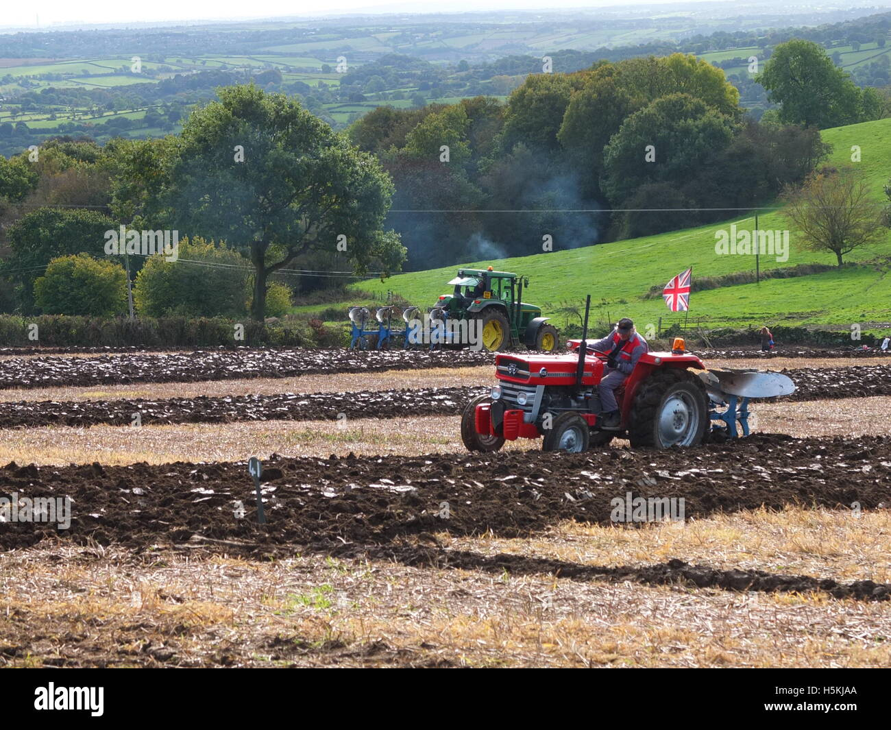A farmer flying the Union Jack flag from his tractor competing in the Ashover Ploughing Match held at Highoredish Stock Photo