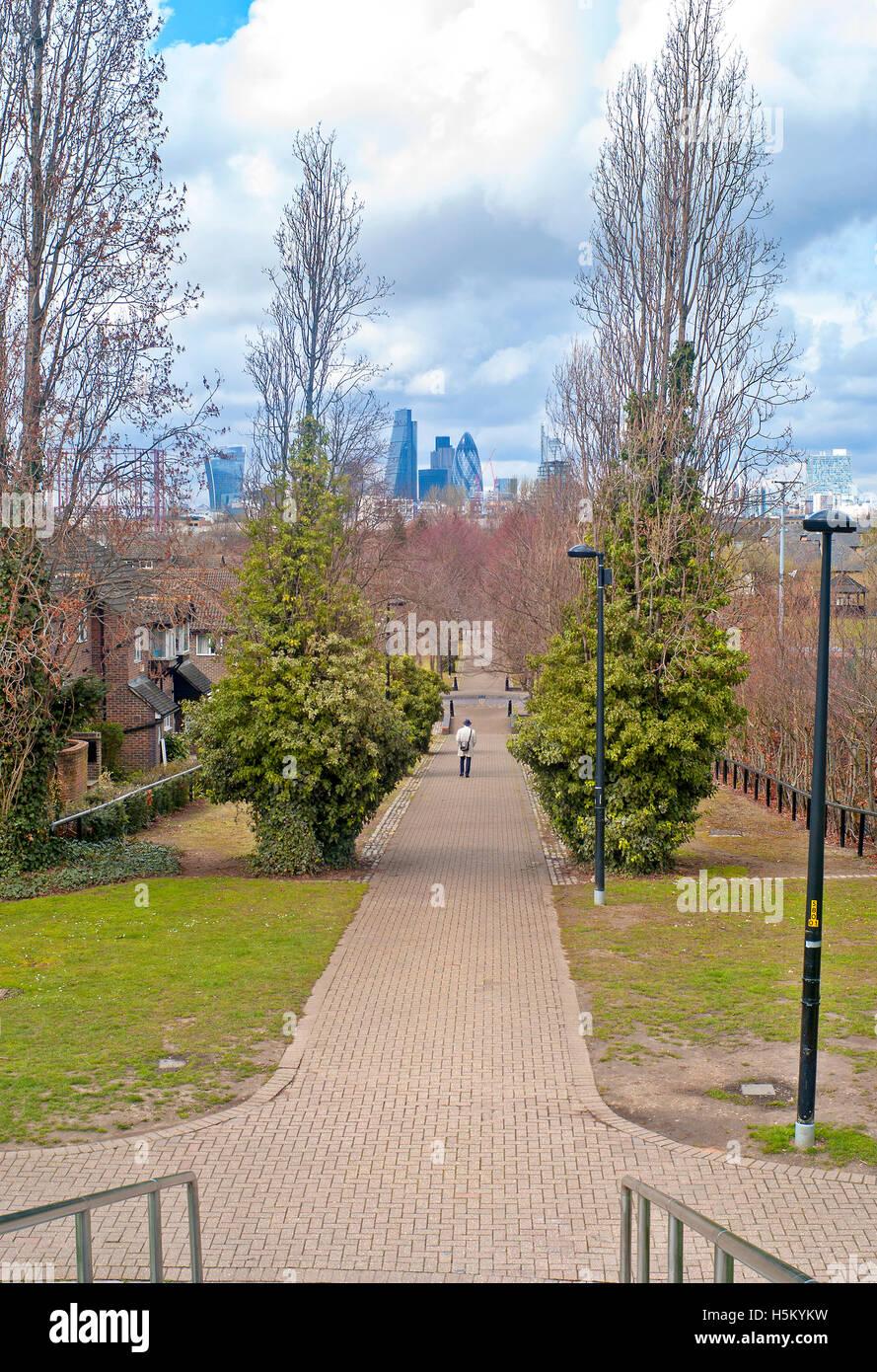 man walking towards city sky line through parkland urban country - Stock Image