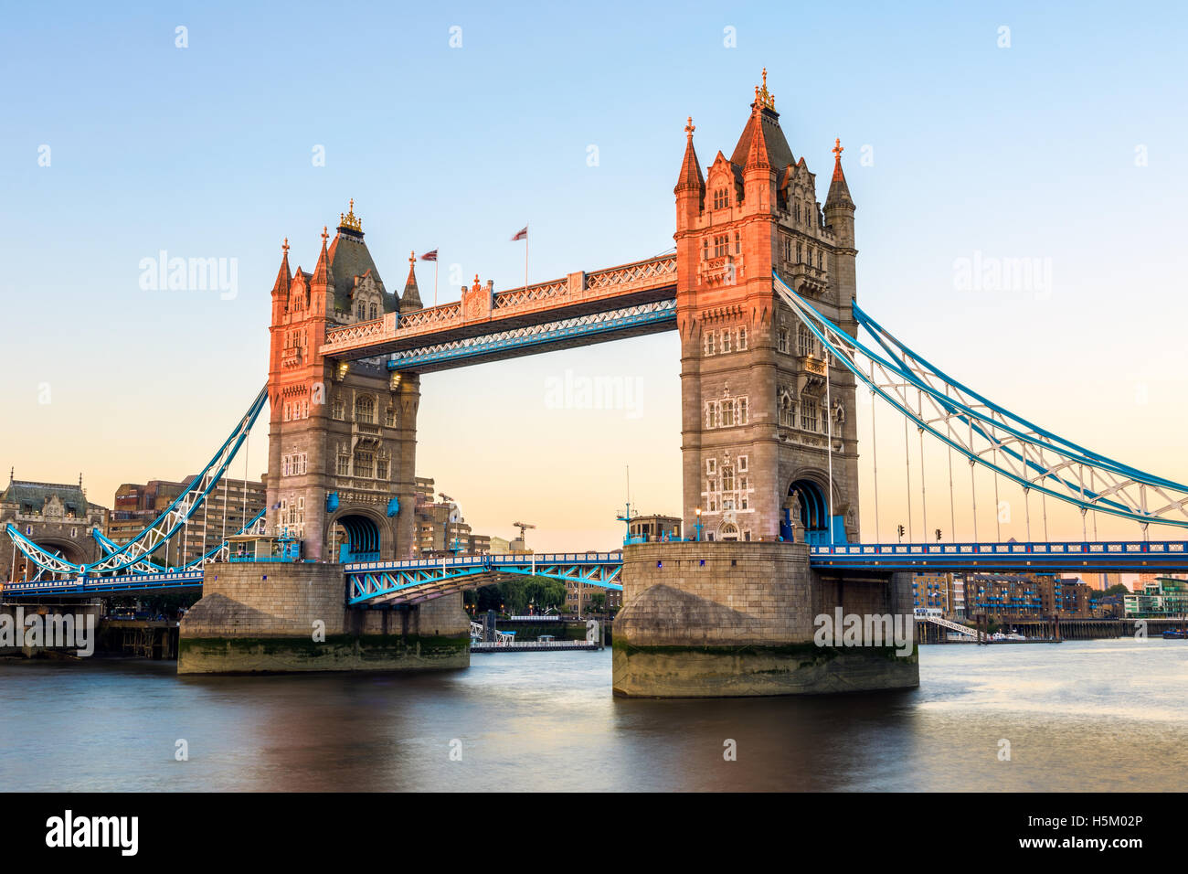 Tower Bridge in London at sunset, casting a orange light on part of the bridge - Stock Image