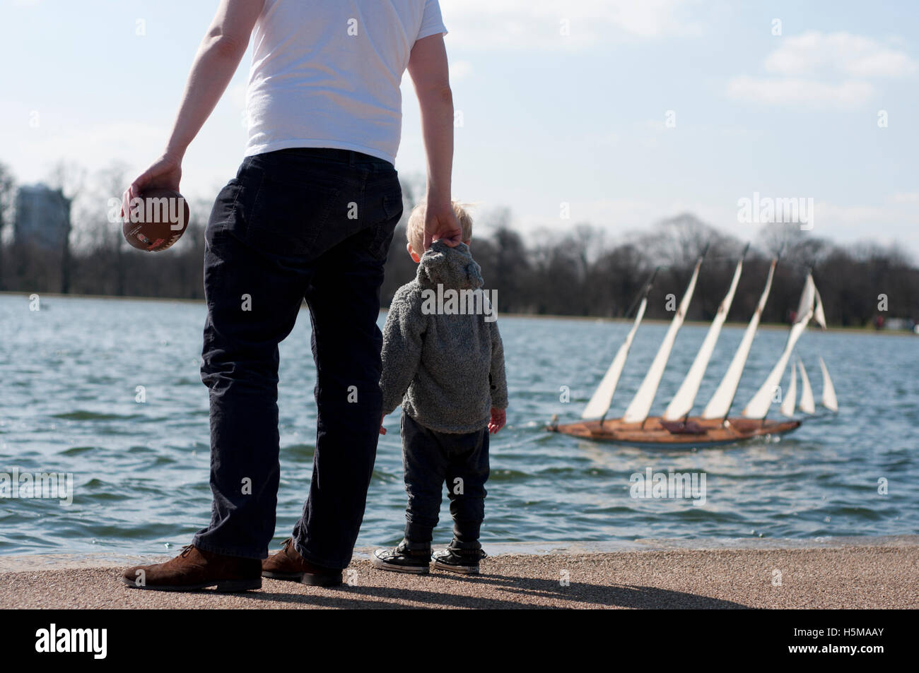 Father and son looking at a miniature boat in London. - Stock Image
