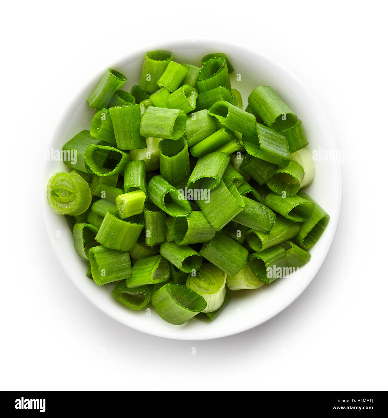 Bowl of chopped spring onions isolated on white background, top view - Stock Image