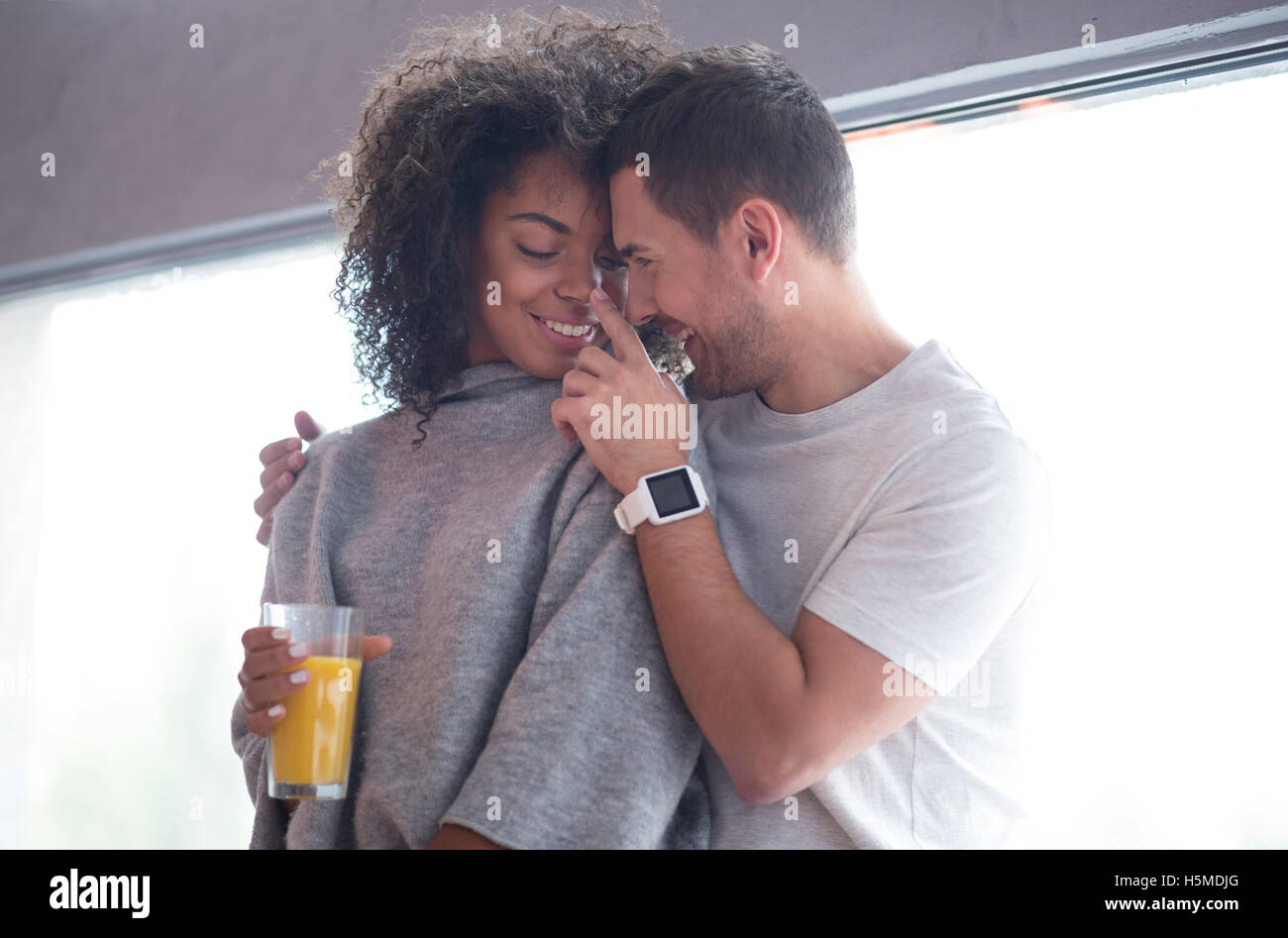 Smiling man touching the nose of his girlfriend tenderly - Stock Image