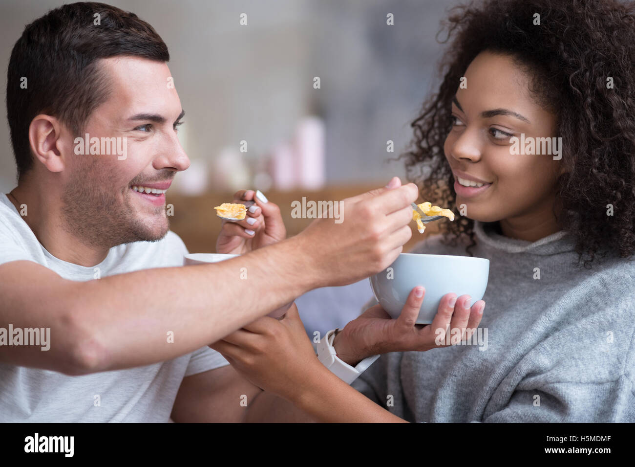 Young couple feeding each other with cereals tenderly - Stock Image
