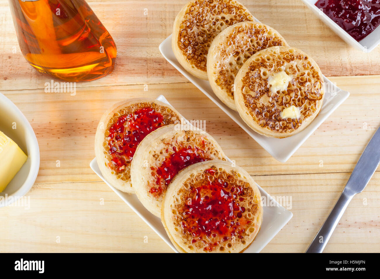 Freshly toasted crumpets on rectangular serving dishes with butter and jam laid out on a country table - Stock Image