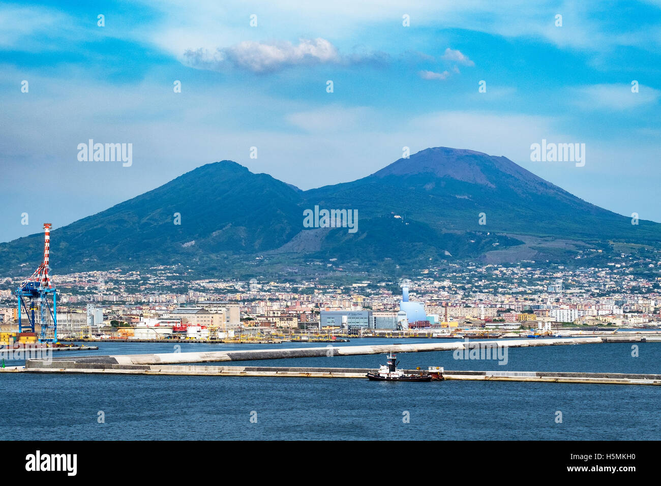 Mount Vesuvius looms over the city of Naples in Italy. - Stock Image
