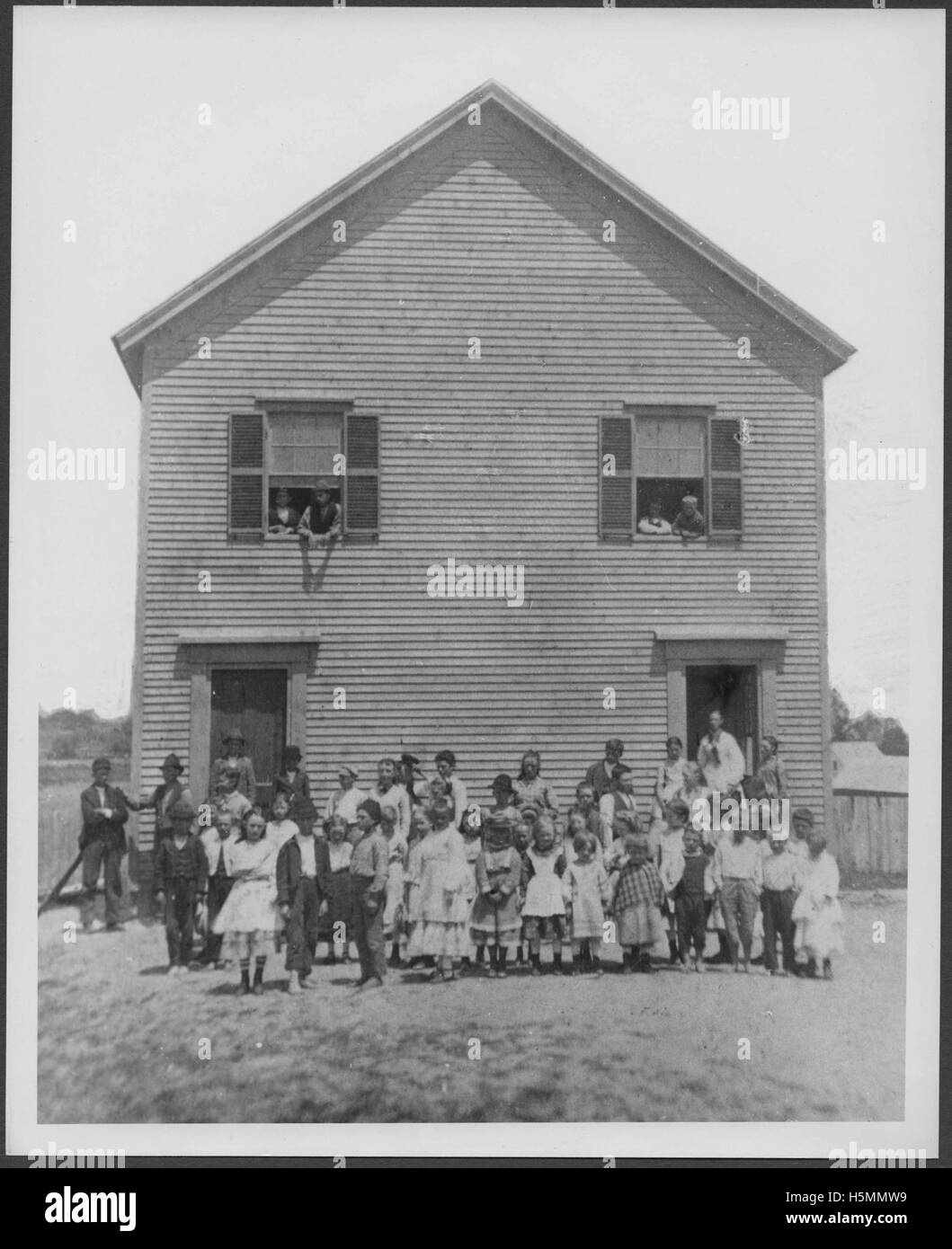 Photograph of the Lincolnville Beach schoolhouse circa 1882.   Children are lined up in front of the school and Stock Photo