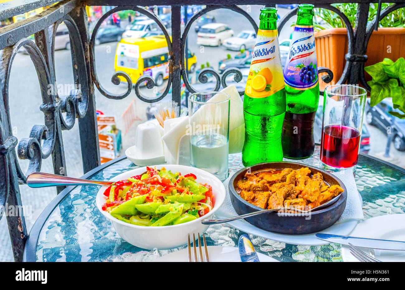 The dinner in outdoor terrace of cafe in old town with vegetable salad, baked veal in souse and Georgian lemonade, - Stock Image