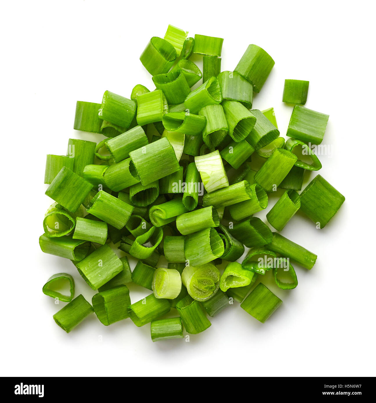 Heap of chopped spring onions isolated on white background, top view - Stock Image