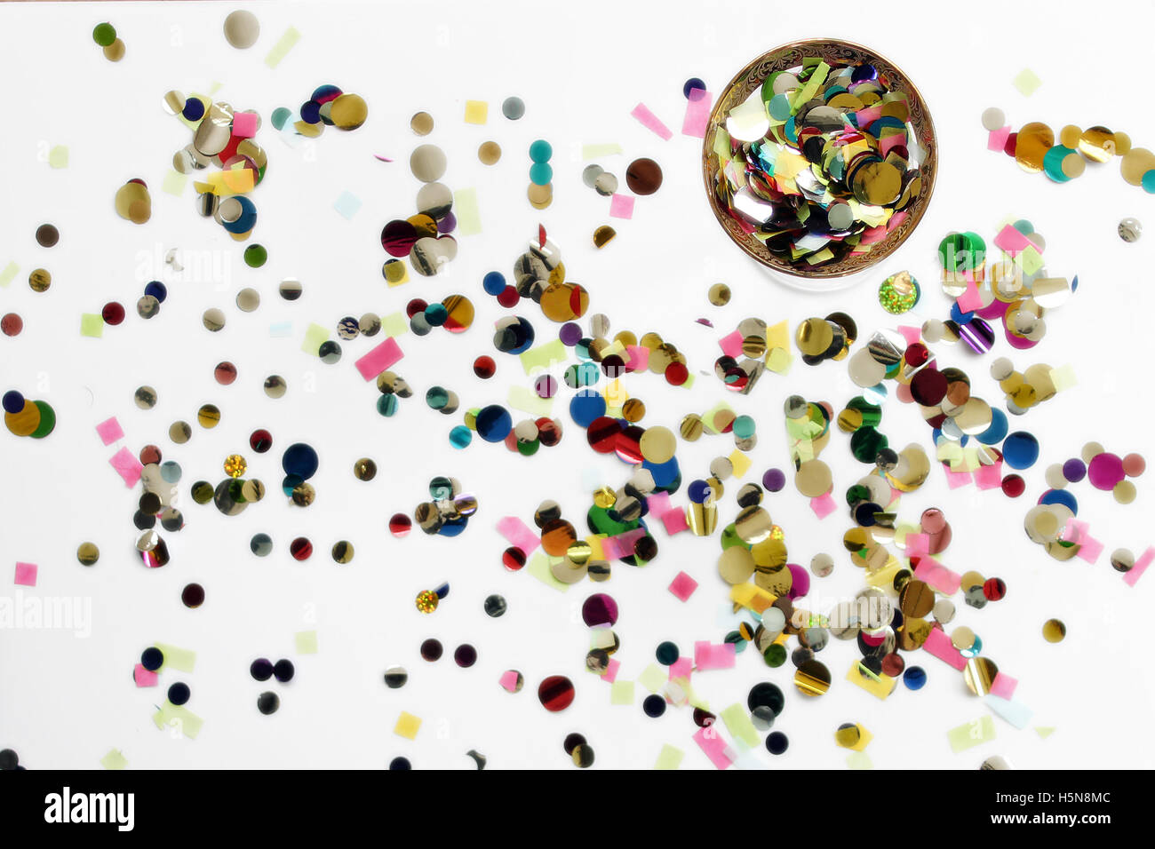 Over head image of a cocktail glass filled with confetti. Confetti spilled on table top - Stock Image