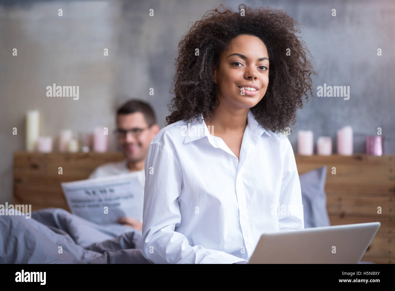 Happy girl using laptop in one bedroom with husband - Stock Image