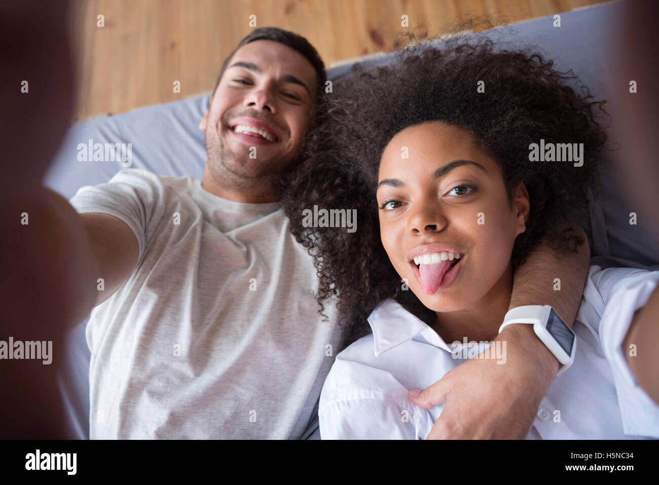 Funny couple putting our their tongues for photo - Stock Image