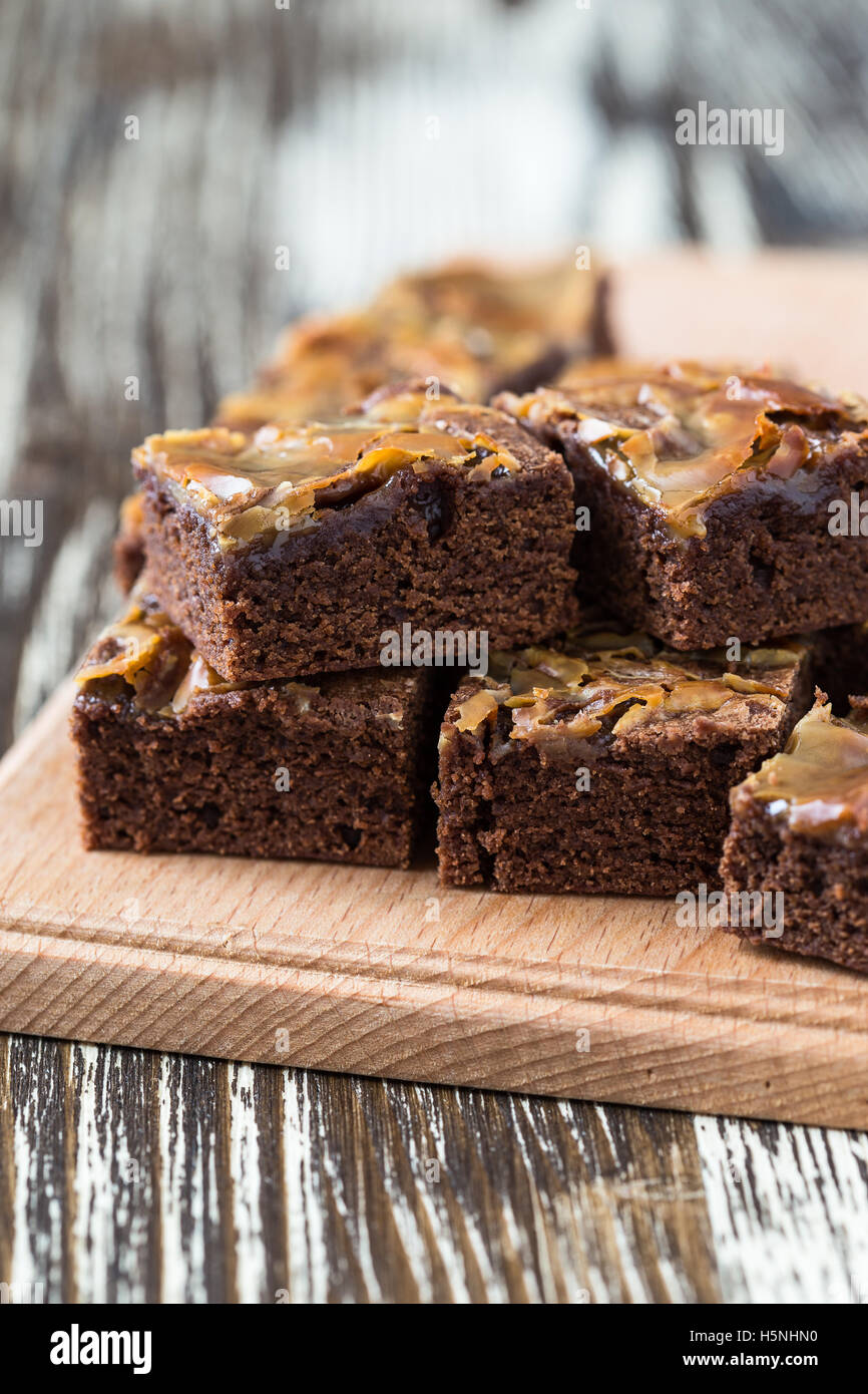 Homemade caramel chocolate brownies on wooden board - Stock Image