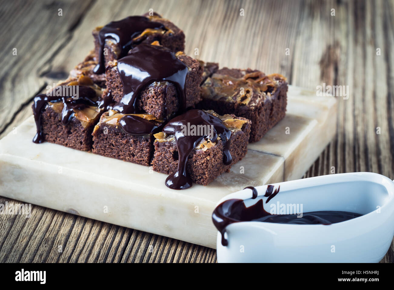Homemade caramel chocolate brownies with dark chocolate ganache served on marble stand Stock Photo