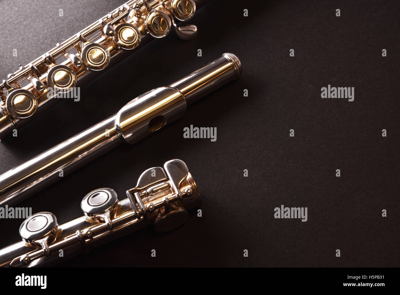 Detail of transverse flute disassembled into three parts on black table. Horizontal composition. Top view - Stock Image