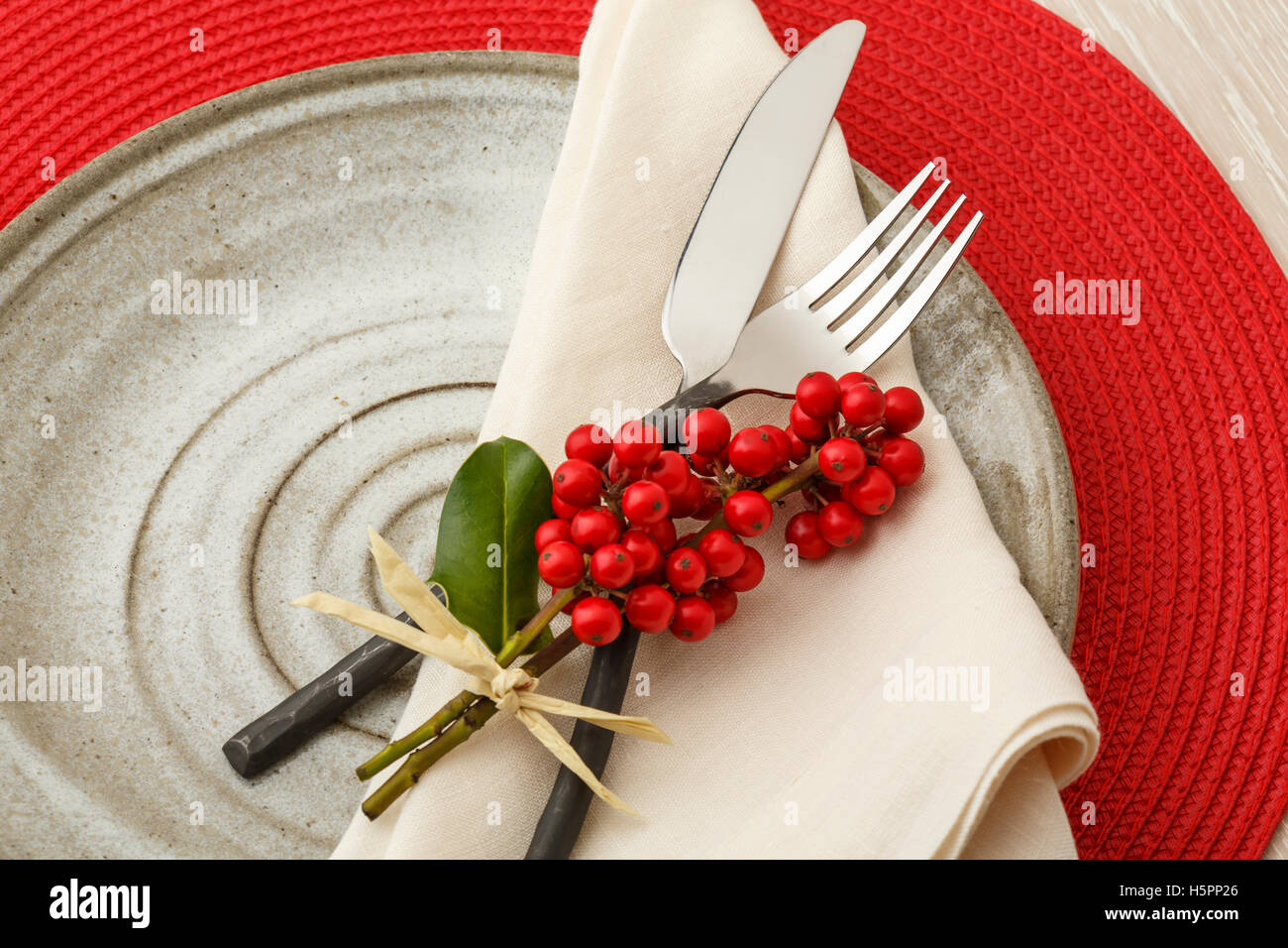 Casual artisanal Christmas table setting place setting with rustic silverware, handmade pottery plate and natural - Stock Image