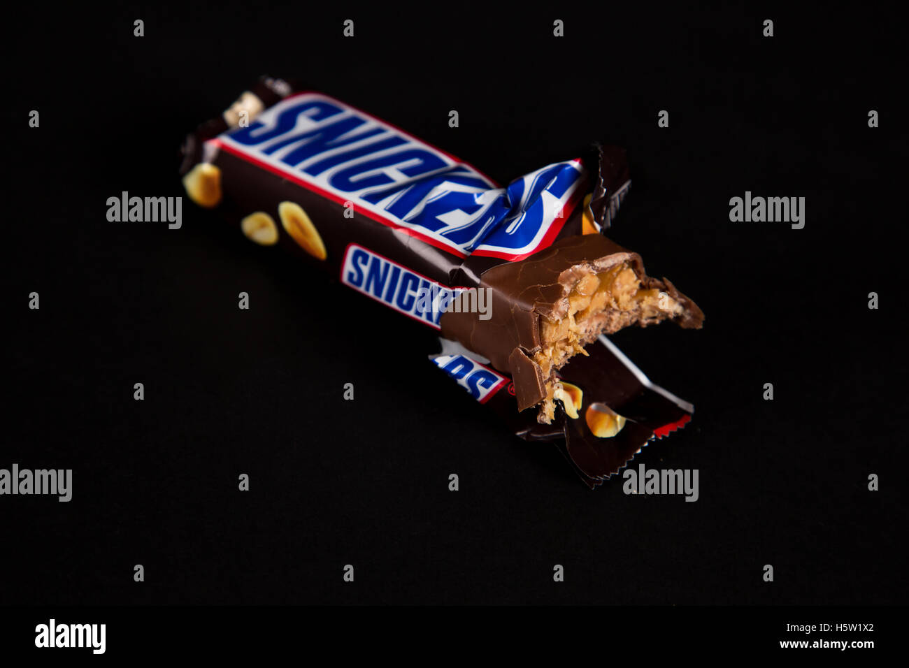 a close up on a snicker bar which somebody has been taking a bite of