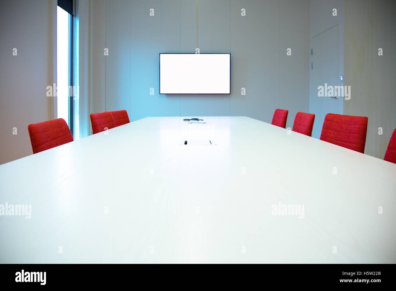 A conference room with chairs and a screen - Stock Image