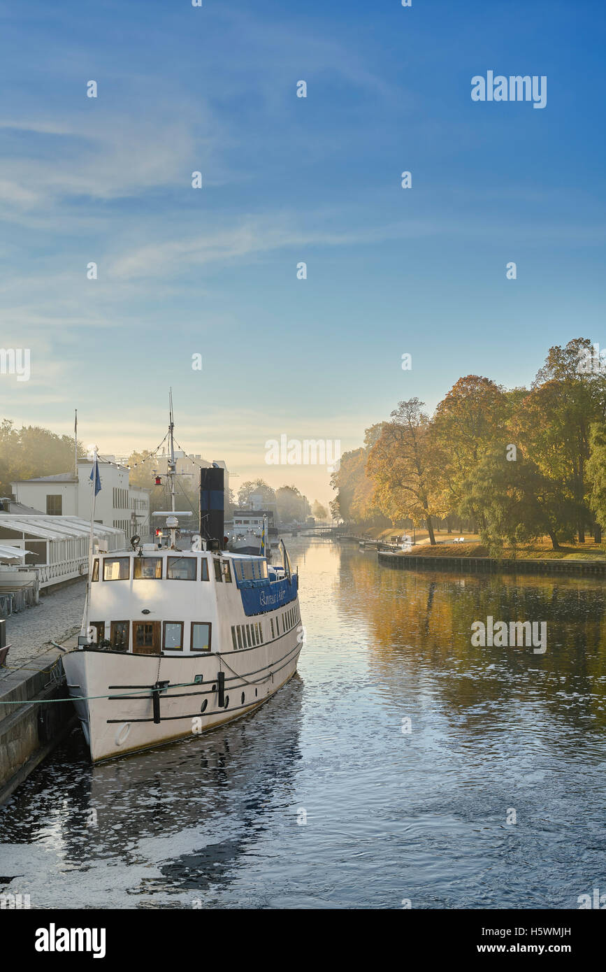 Old steamboat in the Fyris river at a misty autumn morning at Islandsfallet, Uppsala, Sweden, Scandinavia - Stock Image