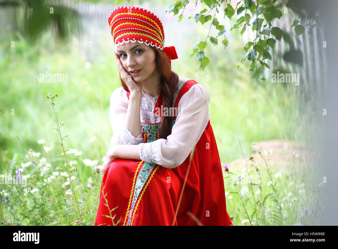 Slav in traditional dress is sitting in nature - Stock Image