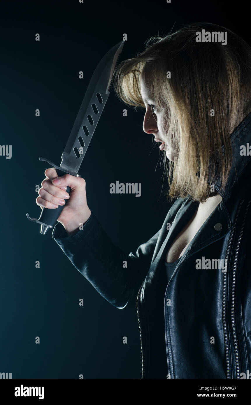 Blonde female holding a dagger in the dark - Stock Image