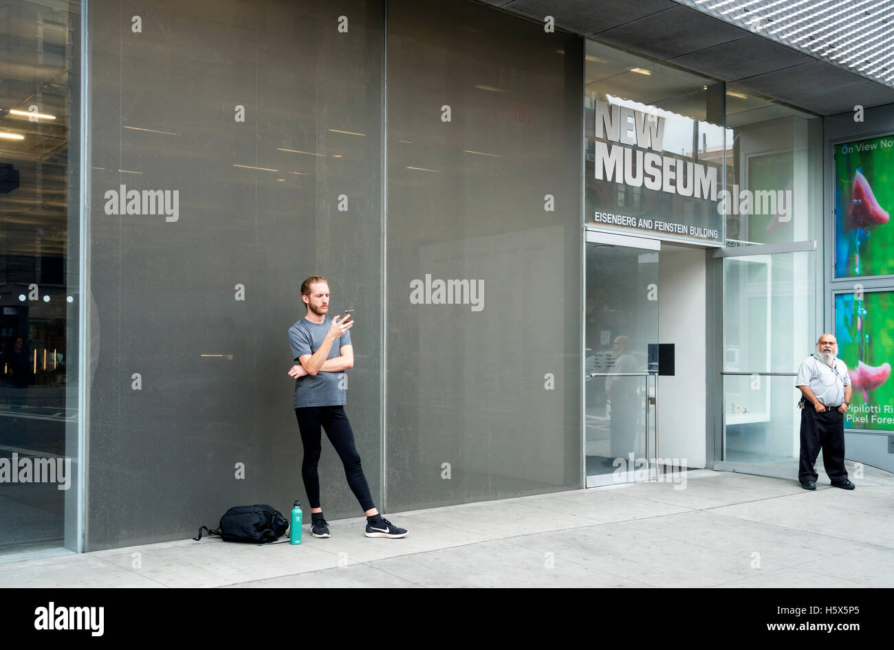 A security guard looking at a male hipster consulting his Smartphone at The New Museum - Stock Image