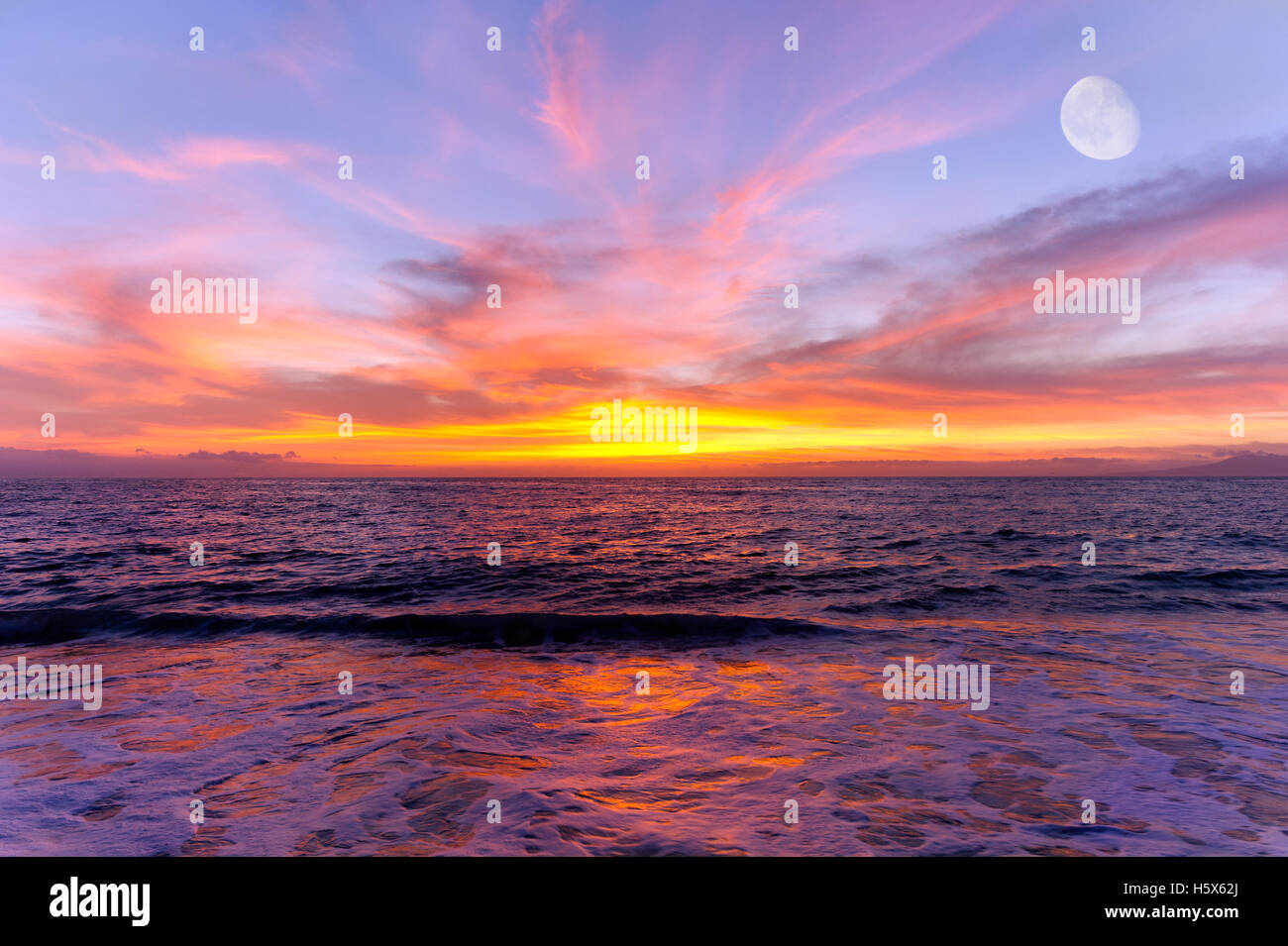 Sunset ocean moon is a colorful scenic ocean sunset setting with the moon rising in the sky. - Stock Image