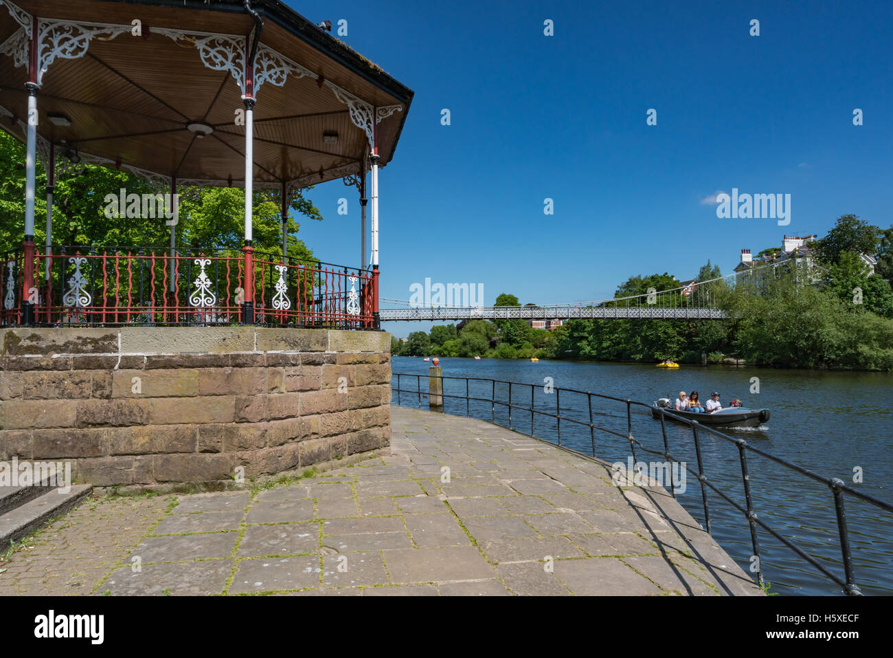 Family in hired motorboat pass the bandstand at Chester Groves on the River Dee - Stock Image