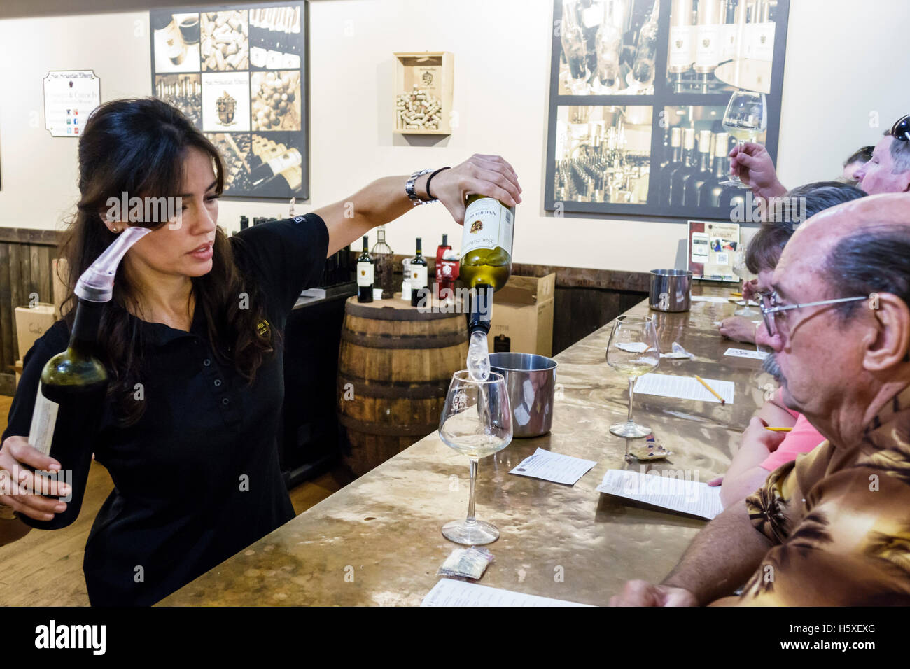 St. Saint Augustine Florida San Sebastian Winery inside wine tasting event woman man Hispanic pouring hostess - Stock Image