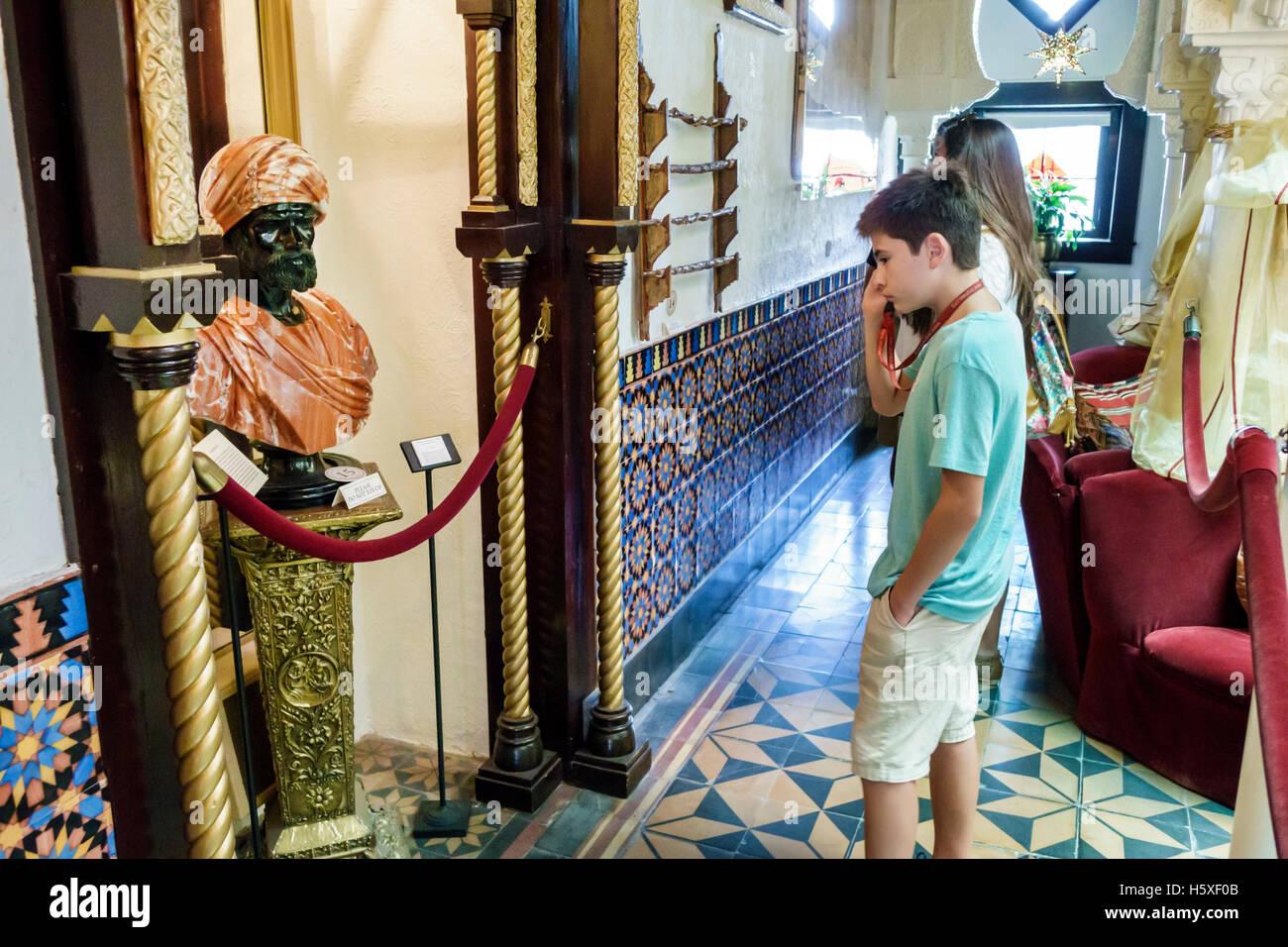St. Saint Augustine Florida Villa Zorayda Museum Moorish Revival inside collection teen boy listening audio guide - Stock Image