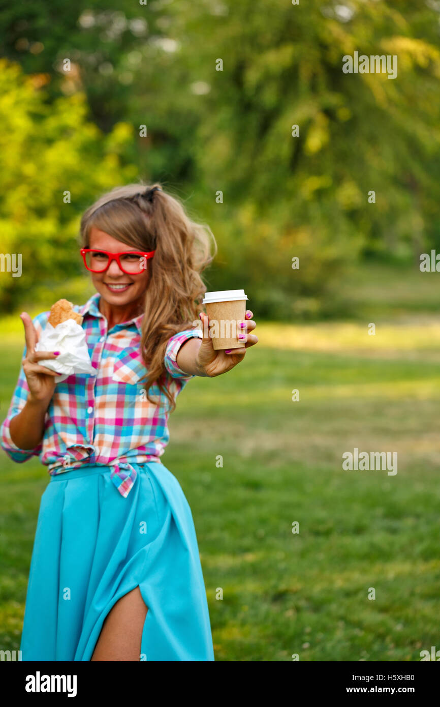 Pretty attractive girl holds cup of coffee and a hot dog in a park. Snack. Fast food. - Stock Image