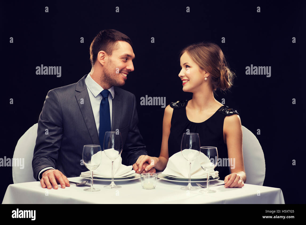 smiling couple looking at each other at restaurant - Stock Image