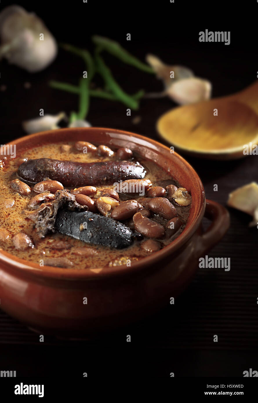 Spanish fabada with Black pudding and sausage in an earthenware dish on rustic background Stock Photo
