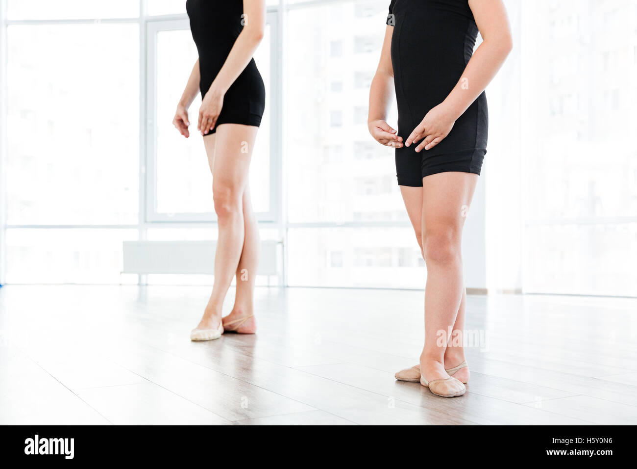 Cropped image of a young female ballet teacher and her little apprentice standing in the same ballet pose - Stock Image