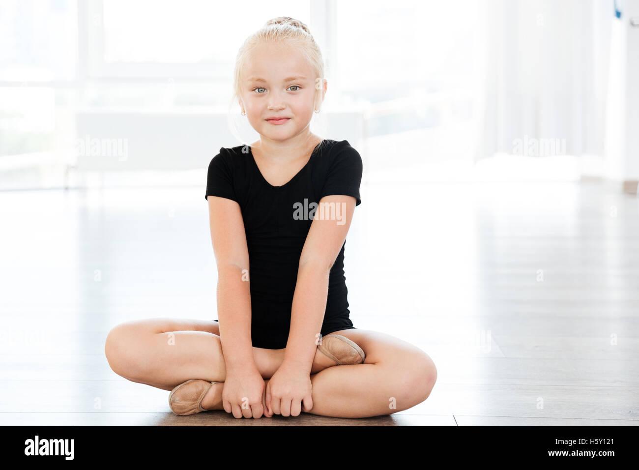 Portrait of happy beautiful little girl ballerina sitting with legs crossed in ballet studio - Stock Image