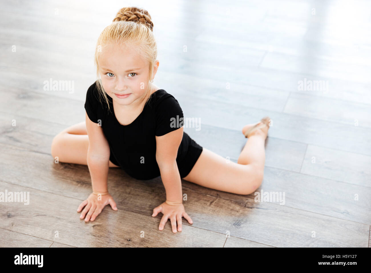 Cute little girl ballerina stretching on the floor in ...