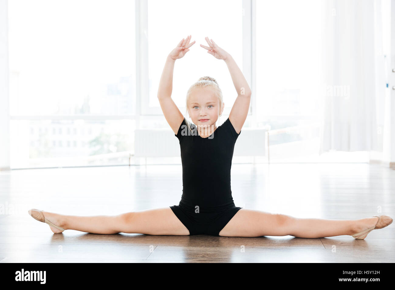 61cd5001fea5 Cute little girl ballerina doing twine on the floor in ballet school ...