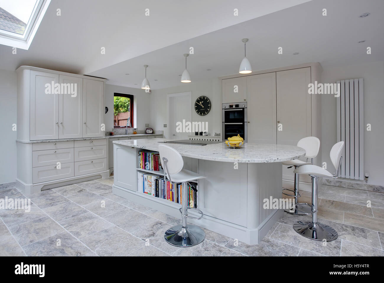 a modern white kitchen with granite worktops in the uk stock photo