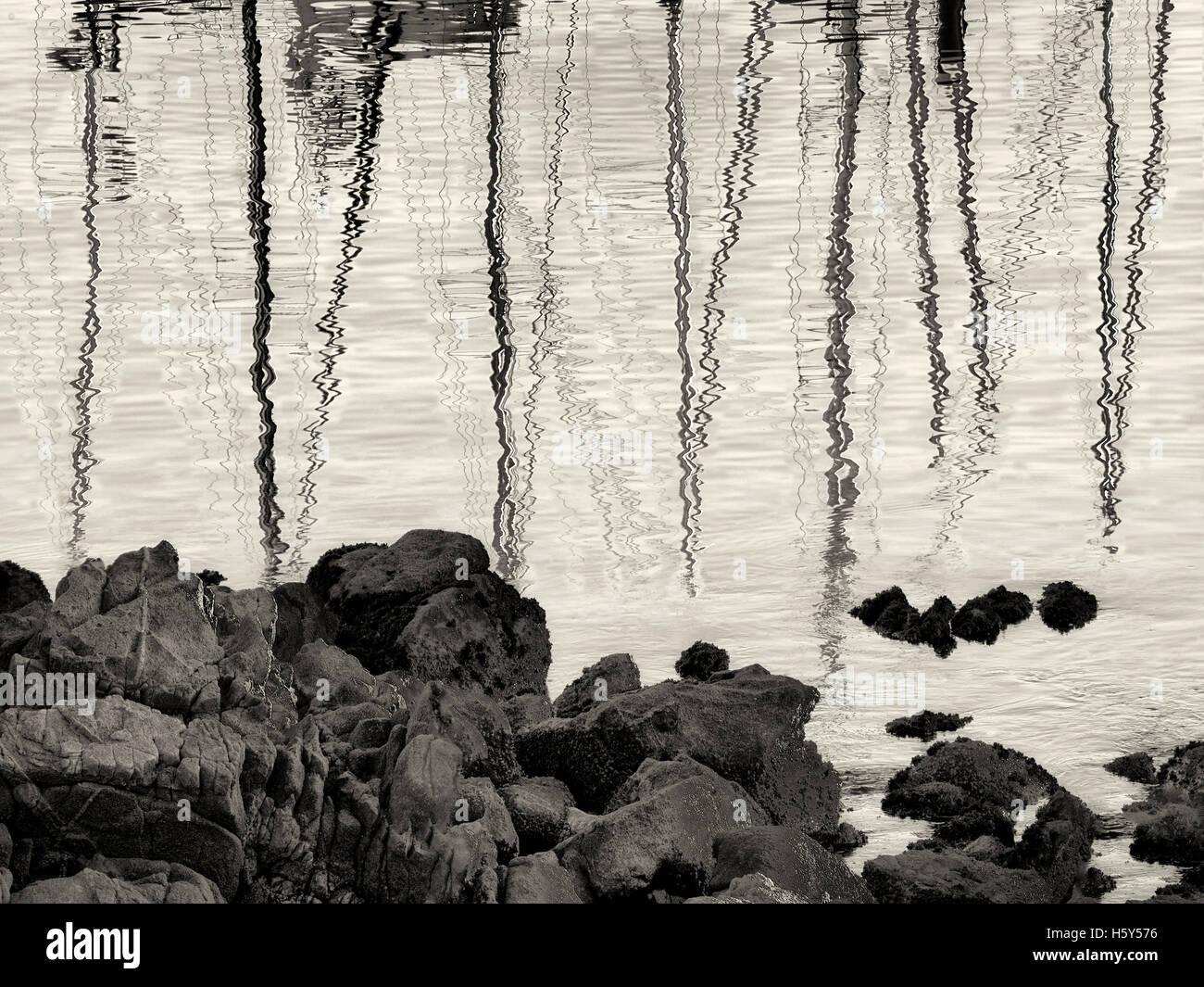 Reflected sailing masts at Monterey Harbor and Marina, California - Stock Image