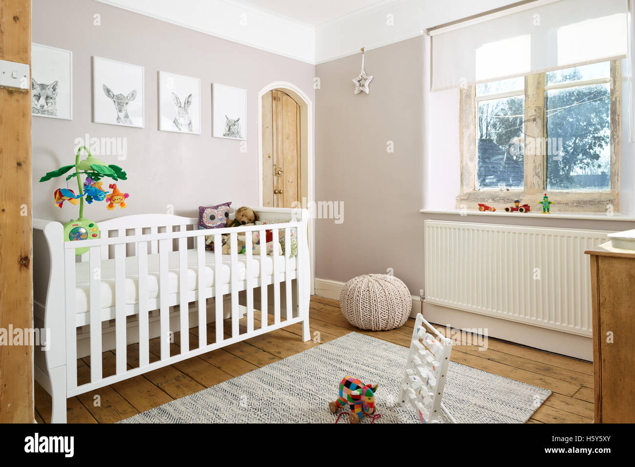 A cot bed in a traditional child's nursery in a modernised British Victorian home - Stock Image