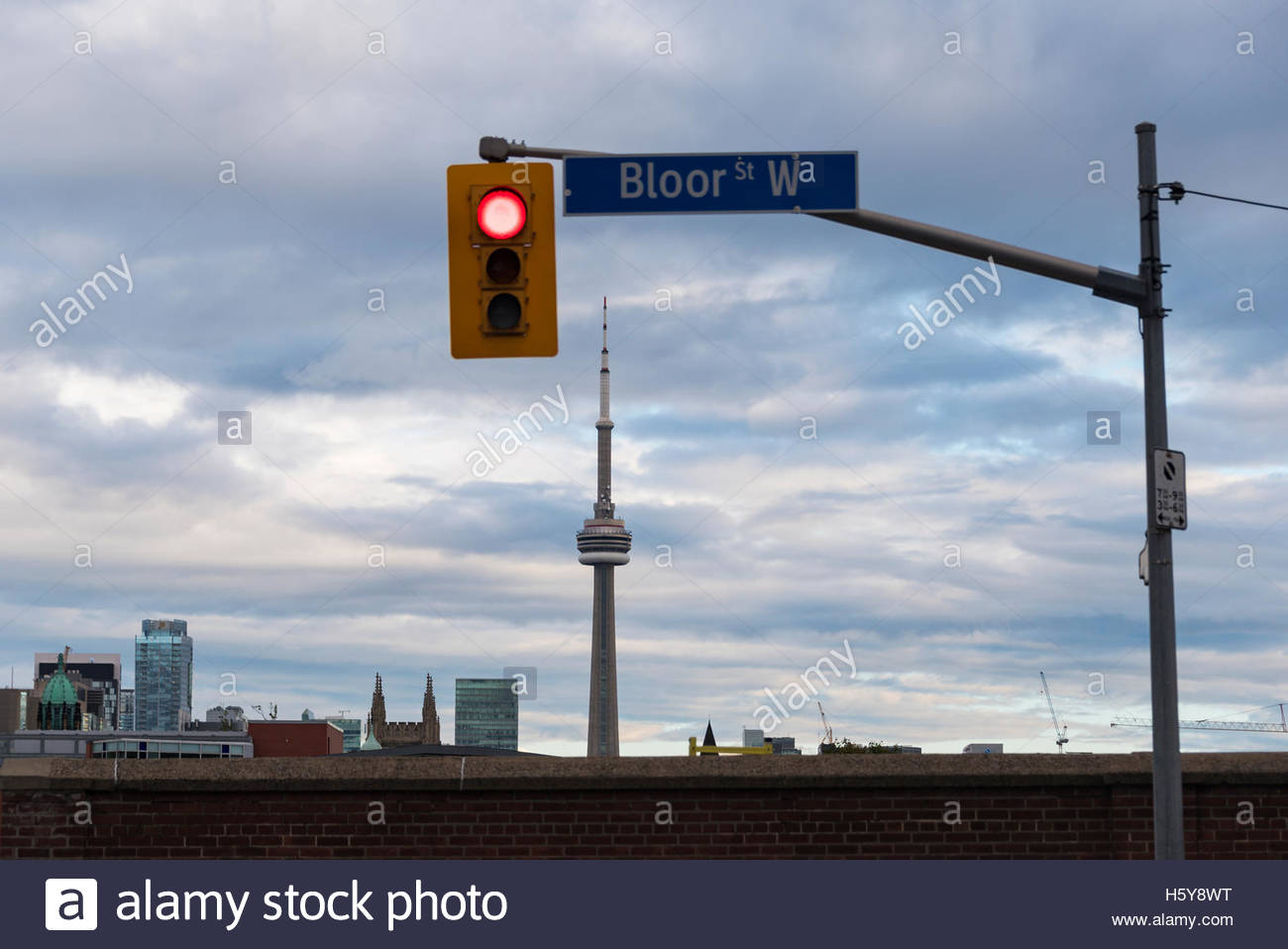 Traffic signal at Bloor street west with CN Tower in the background. - Stock Image