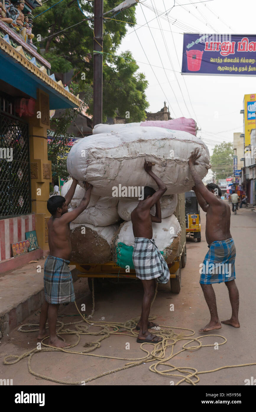 Three men unload huge cotton bales. - Stock Image