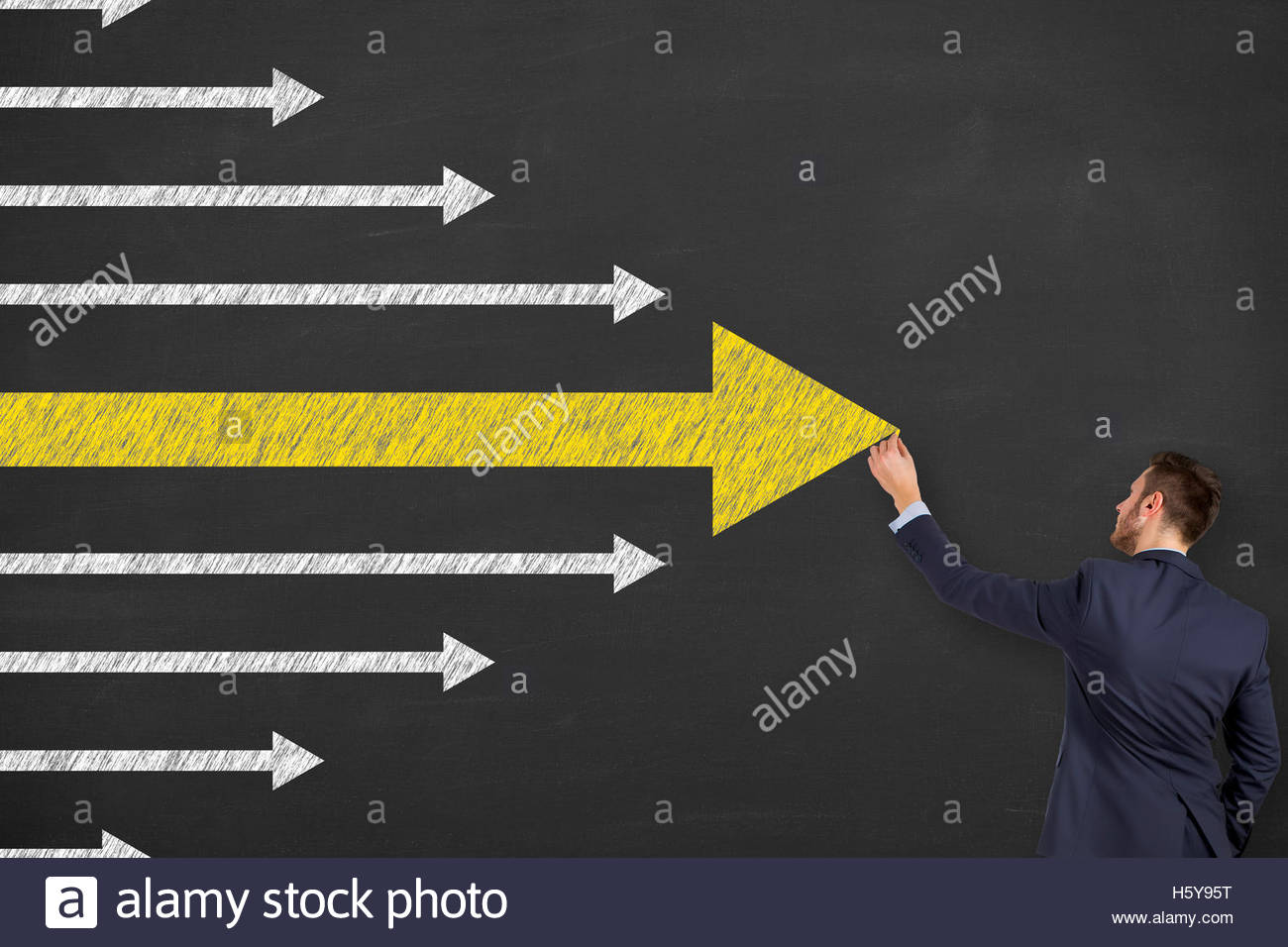 A business man is drawing Leadership concept with arrows on blackboard - Stock Image